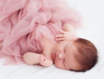 Newborn, two weeks old baby girl in ruffle dress and with finger ring is sleeping peacefully stock photo