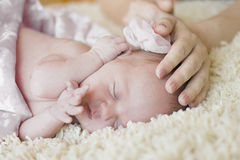 Newborn сute baby girl sleeping and her mother's hand, soothing the baby sleep. Royalty Free Stock Images
