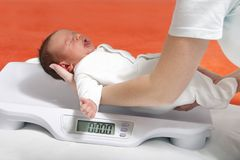 Newborn on weight scale Royalty Free Stock Photo