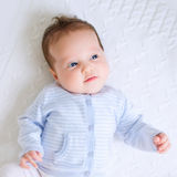 Newborn in white and blue on a white blanket Royalty Free Stock Photos