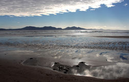 Newborough Beach,  Anglesey, Wales. Dramatic view of Newborough Beach,  Anglesey, Wales. North Wales mountains in the background Royalty Free Stock Photos