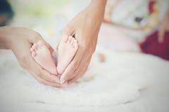 Newbron dziecka cieki w macierzystych rękach Zdjęcie Stock