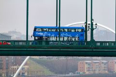 Blue Double Decker bus crossing the Tyne Bridge and Millennium Br. Newcastle, England - March 6, 2018: Blue Double Decker bus crossing the Tyne Bridge and Stock Photo