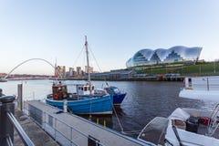 Newcastle kaj med vis man, den Gateshead milleniumbron och boaen fotografering för bildbyråer