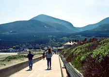 Newcastle, northern ireland. Tourists and townspeople walking in the seaside town of newcastle, northern ireland with the mourne mountains in the distance Stock Photography