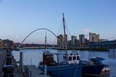 Newcastle Quayside with Gateshead Millenium Bridge and Boat in s. Newcastle Quayside with Gateshead Millenium Bridge, other landmarks  and Boat in sight Royalty Free Stock Photo