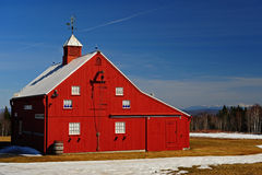 A newer bright red barn and white mountains Stock Images
