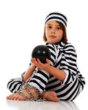 Newest on the Chain Gang. Unhappy elementary child in striped prison garb sitting on the floor holding her ball and chain Royalty Free Stock Photos