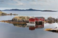 Newfoundland fishing shacks NL Atlantic Canada. Red painted wooden fishing shacks at New Foundland, NL, Canada, Atlantic Ocean coast calm cove royalty free stock image