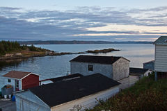 Newfoundland fishing village. Scenic view of traditional fishing shacks at dusk with sea and cloudscape background, Triton village, Newfoundland and Labrador Stock Images