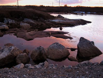 Newfoundland Scenic. Rocks/Gravel and calm waters with a beautiful colorful sky Stock Photo