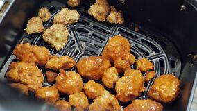 Revealing of cauliflower buffalo bites in air fryer being prepared to cook