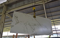 A newly arrived stone slab is being lift to be shown to customer Royalty Free Stock Photo