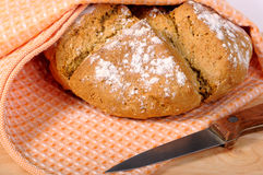 Newly-baked bread. In a dishcloth and a knife stock image