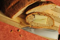 Newly-baked bread. Homemade brown bread with butter Royalty Free Stock Images