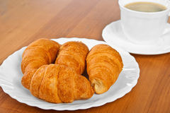 Newly-baked croissants and cup of coffee. Royalty Free Stock Image