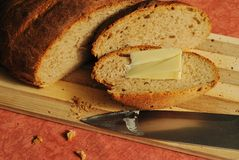 Newly-baked rural bread. Homemade brown bread with butter Royalty Free Stock Photography