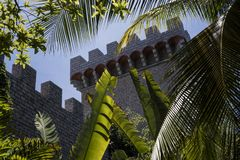 A newly built castle seen through banana trees and coconut trees` leaves in Phan Tiet, Vietnam stock photo