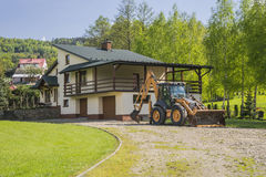 Newly built country house. Newly built small cottage in the forest somewhere in the Polish village and excavator royalty free stock photos