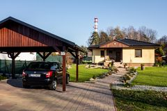 A newly built family house with a wooden garage and a black car. PETRVALD, CZECH REPUBLIC - NOVEMBER 16, 2018: A newly built family house with a wooden garage stock images