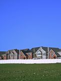 Newly built houses. Row of newly built single-family houses behind a white fence with lots of blue sky and green grass Stock Photos