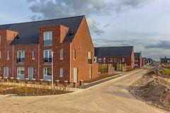 Newly built houses in modern street. Building site in suburb of city in the Netherlands royalty free stock photos