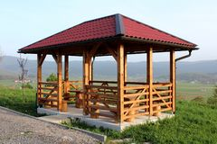 Newly built wooden gazebo structure with new roof mounted on concrete foundation with wooden table and chairs overlooking houses. Newly built wooden gazebo stock photo