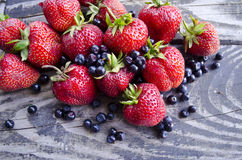 Newly collected fresh blueberries and strawberries on wooden background. Summer organic berry over wood. Stock Photos