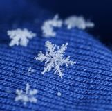 Newly fallen snow flake crystal on blue wool. Newly fallen snow flake crystal on blue knitten wool winter feeling stock photos