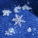 Newly fallen snow flake crystal on blue wool. Newly fallen snow flake crystal on blue knitten wool winter feeling stock photo