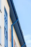 Newly installed blue rain gutter and drainpipe Stock Photography