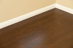 Newly Installed Brown Laminate Flooring and Baseboards in Home. Beautiful Newly Installed Brown Laminate Flooring and Baseboards in Home Stock Photo