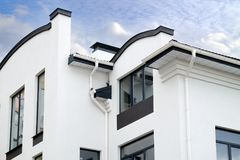 Newly installed construction frame house rain gutter system on the roof top. royalty free stock image