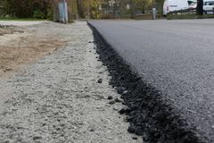 Newly laid black bitumen asphalt with a high edge to the gravel. Freshly laid black bitumen asphalt with a high edge to the gravel showing the structure stock image