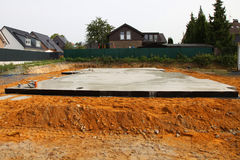 Newly laid floor and foundation. For a house in an urban residential neighbourhood with neighbouring properties visible Stock Photos