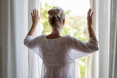 Woman looking out the window in pijama. royalty free stock photos