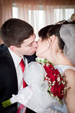 Newly-married couple. Standing near the window and kissing Royalty Free Stock Images