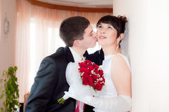 Newly-married couple. Kissing near the wall Royalty Free Stock Photo