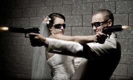 Newly married couple. In white wedding dress, shoot of  black pistols Royalty Free Stock Image