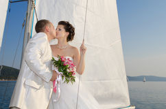 Newly married couple. Vertical photo newly married couple stand on white yacht, outdoor royalty free stock images