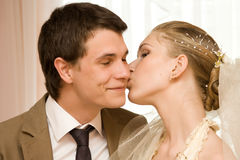 Newly-married couple. Wedding portrait of a newly-married couple. The bride kisses the groom Royalty Free Stock Images
