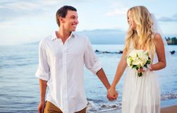 Newly married couple in beach. A married couple, bride and groom, at sunset on a beautiful tropical beach Stock Photos