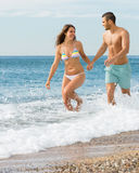 Newly married couple at the beach. Happy smiling newly married couple having honeymoon at tropical beach Stock Photography