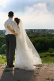 Newly-married couple. Beautiful the bride and groom on landscape background Royalty Free Stock Images
