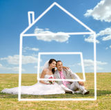 Newly married couple. Beautiful newly married couple  on nature in park , sit on  lawn and dreaming about house Royalty Free Stock Photo