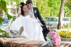 Newly-married couple on a bench in park Stock Image