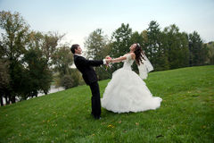 Newly married couple dancing in field Stock Photos