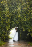 Newly married couple dancing at tunnel in trees Stock Photo