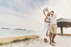 Newly married couple with digital tablet on pier Stock Images