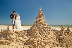 Newly-married couple enjoying on the beach. A young and beautiful newly-married couple enjoying on the beach near sandy castle at the sea edge Royalty Free Stock Image